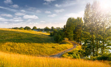 Amazing nature scenery. Summer landscape at sunny day. perfect countryside scenery with blue sky and grassy hillside, glowing sunlit.