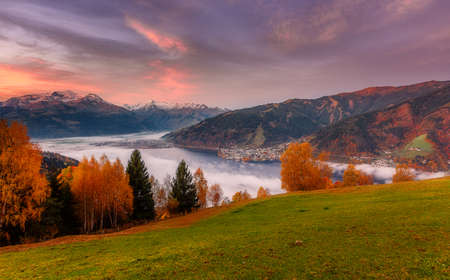 Incredible Nature Landscape., foggy morning during sunrise at Alpine lake in autumn. Colorful Sky over the Zeller Lake in Zell am See, Salzburger Land, Austria. Creative image. Natural Background