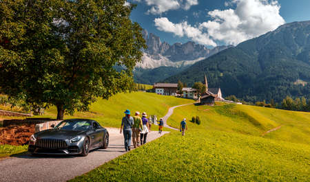 luxury car and hikers on road. of a Best beautiful place in the World Santa Maddalena. Dolomites Alps. Italy. is one of the most popular photo spot of Dolomite. Famous World place.  Summer Landscape