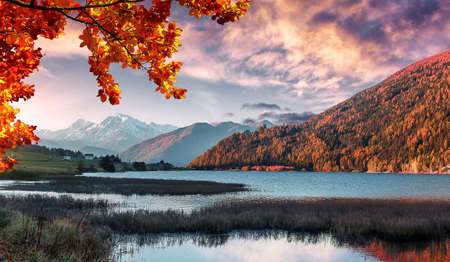 Wonderful Alpine Landscape in Sunny day. Colorful Autumn scene. Picture of wild area. Stunning Scenery during sunset, Fantastic Colorful clouds over the mountain lake in alps.