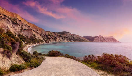 Colorful sunset on the beach on the greek island. Nature in twilight period which including of sunrise over the sea and the nice beach. Summer beach with blue water and purple sky at the sunrise. 版權商用圖片