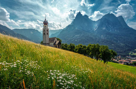 Beautiful view of San Church in Castelrotto village. Idyllic alpine mountain scenery with fresh green grass on meadows and majestic mountain peaks on a sunny day with blue sky in springtime.
