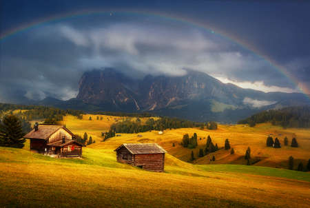 Incredible Nature landscape. Fantastic Dramatic Scenery of Alpe di Siusi or Seiser Alm during sunset with overcast sky and rainbow. Dolomites Alps, Sassolungo peak, Italy, Europe. Creative Image