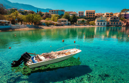 Wonderful Sunny seascape of Asos village, Kefalonia Island. Greece. Sunny spring seascape. boat in azure clear Water of Ionian Sea under sunlit. Beautiful landscape with bay and colorful buildings Banque d'images