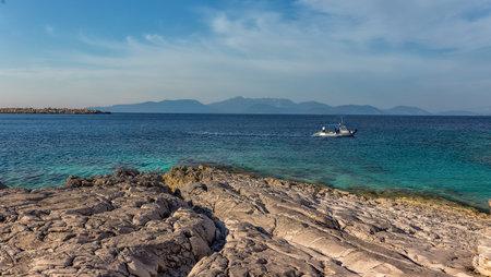 Rocky beach landscape at dusk. Wonderful Seascape during sunset. Coastal landscape of rocky beach calm sea and blue sky. Amazimg greece