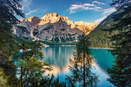 Incredible view on majestic famouse lake Braies during sunrise. Wonderful sunny landscape in dolomites Alps with perfect sky. Amazing nature Scenery. Lake Braies is also known as Lago di Braies.
