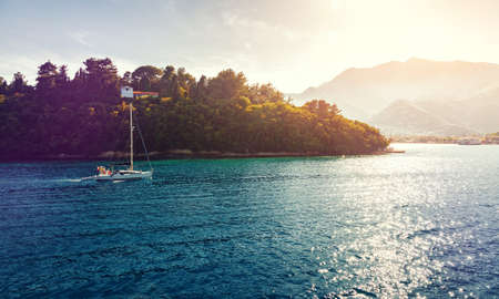 Picturesque Greece landscape with yacht during sunset. Wonderful colorful seascape