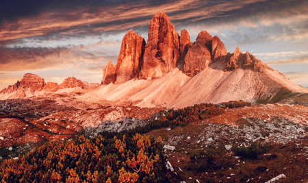 Awesome alpine highlands during sunset. Amasing nature landscape. Tre Cime di Laveredo, three spectacular mountain peaks with colorful sky, Dolomites Alps, South Tyrol, Italy. Picture of wild area 版權商用圖片
