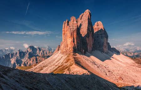 Unsurpassed sunrise in the Dolomites Alps. Famous mountain range with flowers, Tre cime di Lavaredo peak between colorful clouds in spring time, Wonderful Nature Landscape. Italy. Dolomites Alps