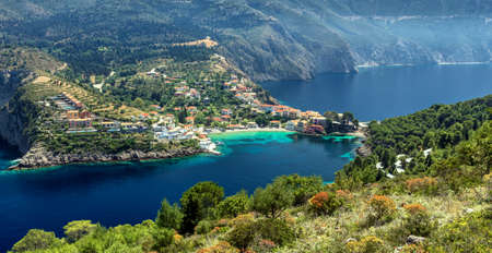 Amazing coastline with colorful houses under sunlight. Wonderful summer seascape with perfect blue sky of Ionian Sea. Assos village. Kefalonia. Greece. aerial shot
