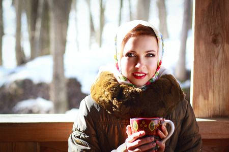 Russian woman in a scarf and coat holding a cup and smiling in a village photo