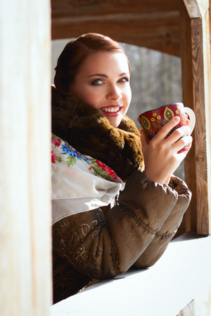 Russian woman holding a cup and smiling in a village photo