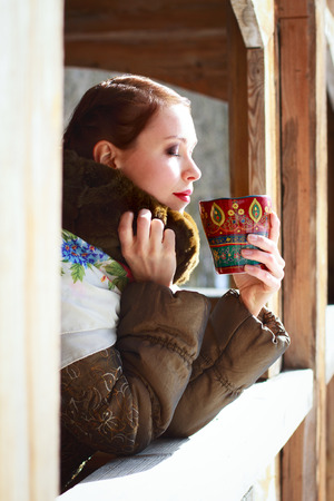 Russian woman drinking tea with closed eyes photo