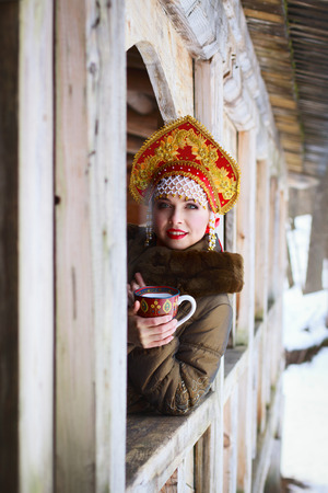 Russian woman in a kokoshnik a smiling in a village photo