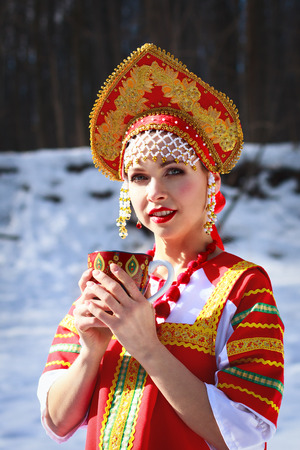 Russian girl drinking tea in a kokoshnik photo
