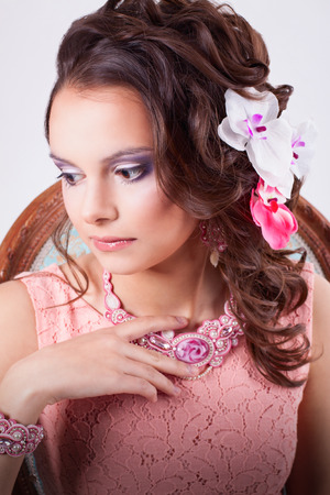 portrait of curly brunette with purple make-up in pink dress with soutache technique decorations with flowers in her hair on a white background photo