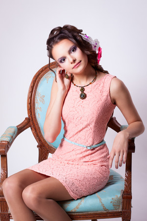 Portrait of curly brunette with purple make-up in pink dress with green soutache technique decorations with flowers in her hair on a white background. Girl sitting on a chair in baroque turquoise photo