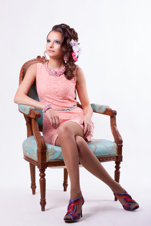 curly-haired brunette in pink dress with soutache technique decorations with flowers sitting on a chair in baroque style on a white background photo