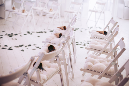 Flower bouquets for guests on chairs at the wedding ceremony