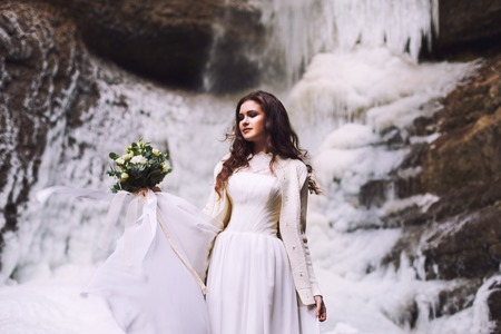 Beautiful young girl in a wedding dress against a background of a glacier in the mountains Stock Photo