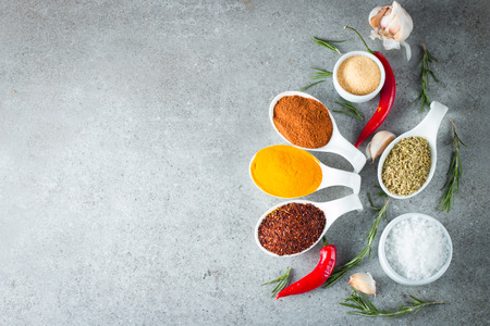 Spices in Wooden spoon. Herbs. Curry, Saffron, turmeric, rosemary, cinnamon, garlic, pepper, anise on wooden rustic background. Collection of spices and herbs. Salt, paprika. Copy space. Top view. Banner. Flat lay.