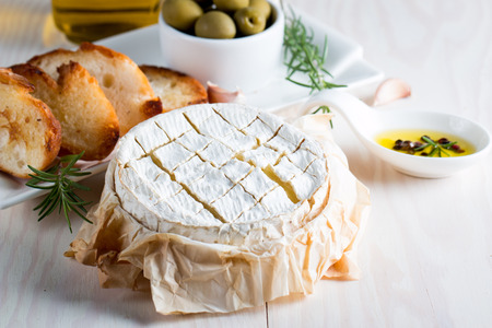 Baked camembert cheese. Fresh Brie cheese and a slice on a wooden board with nuts, honey, rosemary, baguette bread grilled toasts and leaves. Brie type of cheese. Italian, French cheese. Reklamní fotografie - 117122442