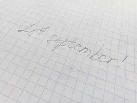 Handwritten inscription in pencil on the first of september on squared paper. Preparation for school, , the beginning of the school year, September 1, a sheet in a cage 写真素材