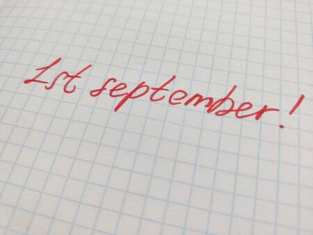 Handwritten inscription in felt-tip pen on the first of september on squared paper. Preparation for school, the beginning of the school year, September 1, a sheet in a cage