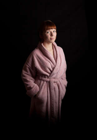red bathrobe: a young adult woman in a pink bathrobe Stock Photo