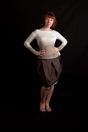 a young adult woman wearing sweater and skirt posing