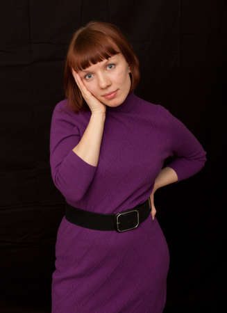 a young adult woman wearing a purple dress looking uncertain