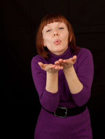 a young adult woman wearing a purple dress sending kisses Stock Photo - 8651628