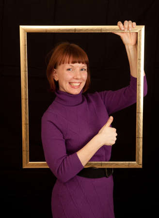 a young adult woman holding a frame showing thumb up