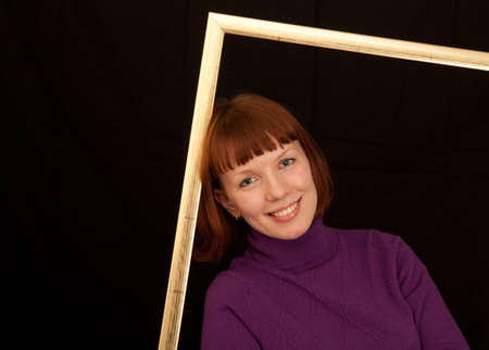 a closeup of a young adult woman leaning in a picture frame photo