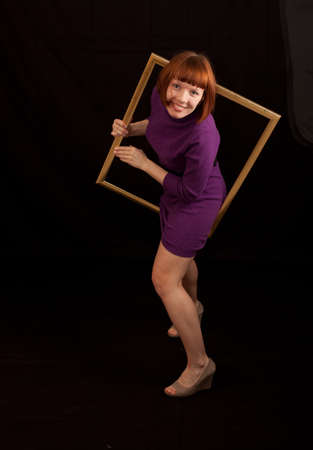 a young adult womand trying to climb throug a picture frame