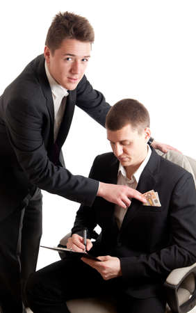 bribing: a young businessmen signing a contract while receiving money