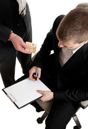 bribing: a young businessman being bribed while signing contract Stock Photo