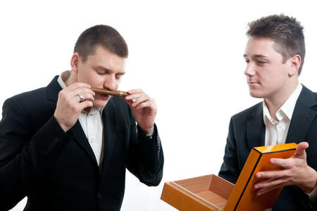 a young businessman smelling the scent of a cigar been offered by another Stock Photo
