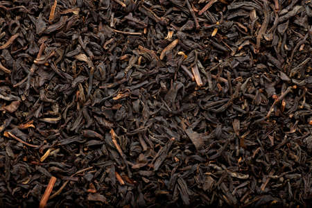 red tea: some dried and fermented black tea leaves forming a background pattern