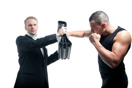 a young businessmen defending a punch with his briefcase