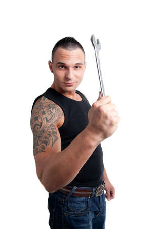 a casual dressed young man with tattoo holding a wrench