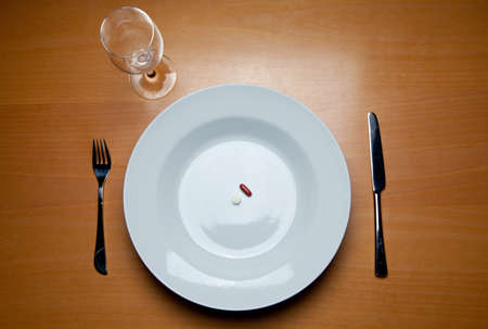 a plate with some pills, cutlery and a wine glass on a wood table Stock Photo