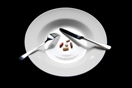 some pills on a plate and cutlery isolated on black photo
