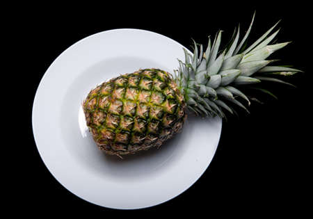 a whole pinapple on a plate isolated on black background Stock Photo