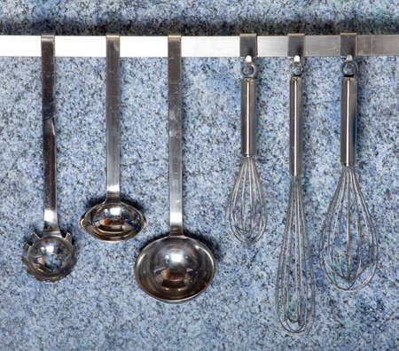 some kitchen tools hanging on a rack in front of a blue granite wall