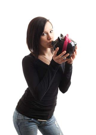 coinbank: una joven besando una hucha aislada en blanco Foto de archivo