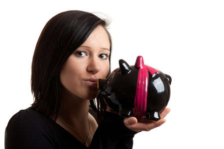 coinbank: closeup of a young woman kissing a piggy bank isolated on white