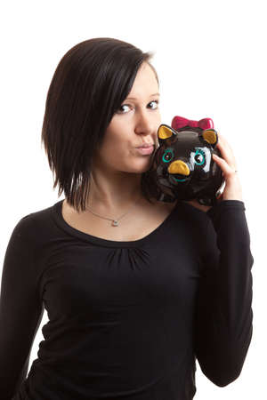 a young woman kissing a piggy bank on her shoulder isolated on white Stock Photo - 9174023