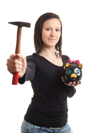 a young woman holding a piggy bank and a hammer isolated on white