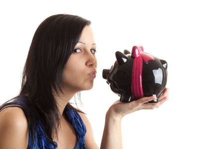 a young woman kissing a piggy bank isolated on white